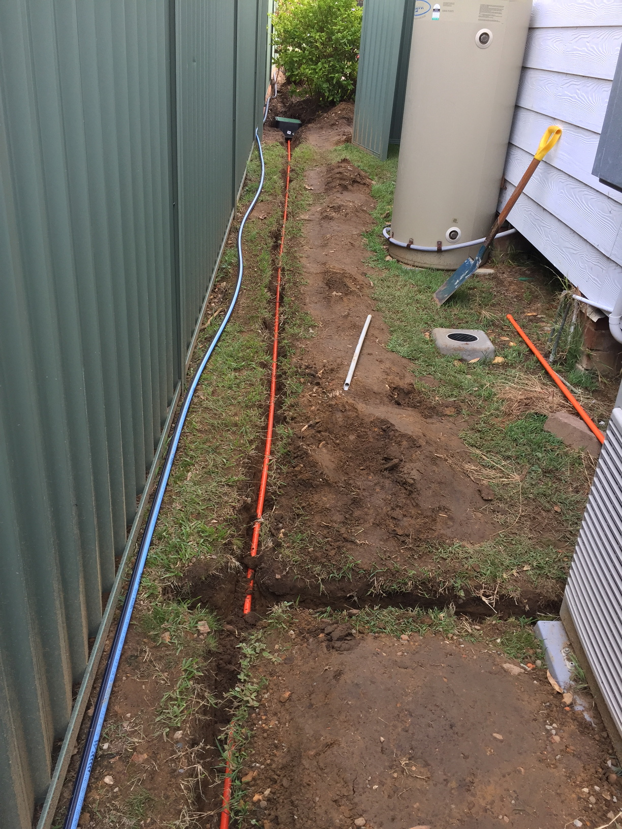 Trench with electrical conduit (orange) running to valve boxes on east side of house and to enclosure (out of shot, mounted on the wall near the air-conditioner compressor)